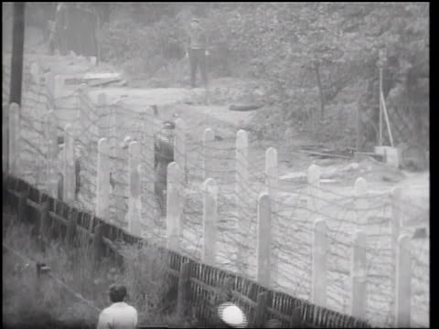 vídeos de stock, filmes e b-roll de guards trying to stop two people from escaping thru barbed wire fence of berlin wall - arame