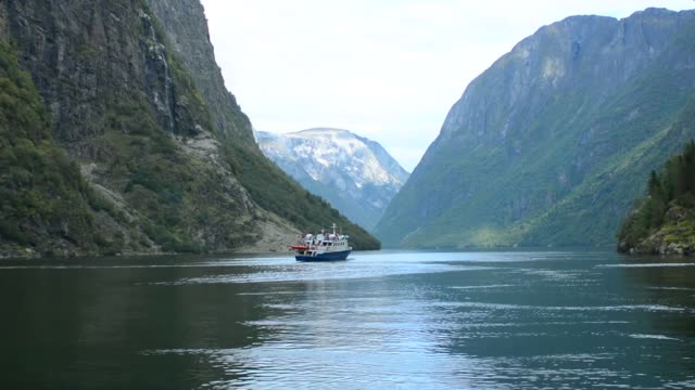 vídeos de stock e filmes b-roll de gudvangen norway  fjord called naeroyforden fjord with ferry boat in valley - noruega