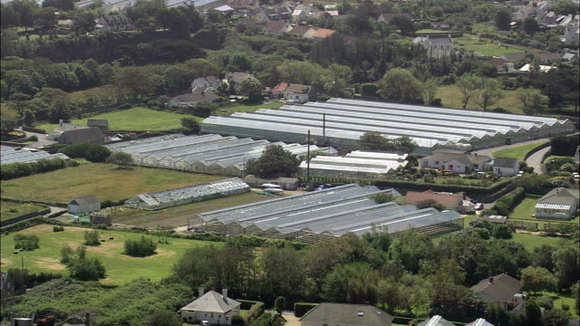 guernsey greenhouses - aerial view - vale,  helicopter filming,  aerial video,  cineflex,  establishing shot,  guernsey - guernsey stock videos & royalty-free footage