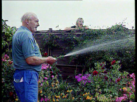 Water Restrictions ITN Channel Islands Guernsey Hotelier Roger Edwards filling pool GVs Reservoir SIDE Man using hose to water garden Another man...