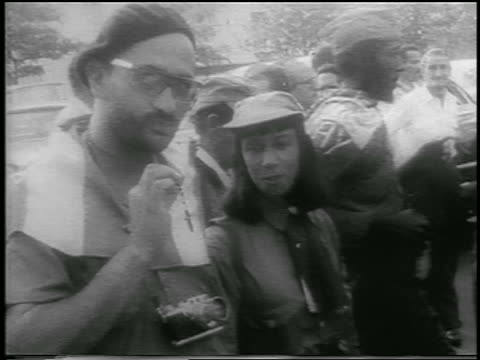 b/w 1959 guerrilla soldier holding rosary with woman smiling beside him / cuba / newsreel - 1959 stock-videos und b-roll-filmmaterial