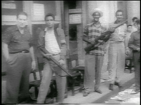 pan guerrilla soldiers holding rifles standing on sidewalk / cuba / newsreel - 1959 stock videos & royalty-free footage
