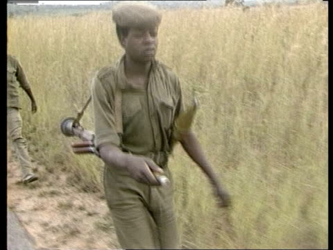 vídeos de stock e filmes b-roll de ext squad of frelimo soldiers patrolling underground oil pipeline to zimbabwe soldiers along road above pipeline past electricity pylons frelimo... - moçambique
