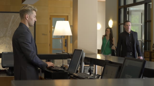 guest arriving at receptionist desk - hotel stock-videos und b-roll-filmmaterial