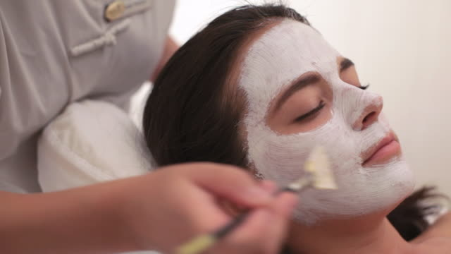 vídeos de stock e filmes b-roll de  pan guest having mask applied during spa facial treatment / stowe, vermont, united states - amimar