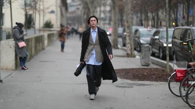 A guest is seen wearing blue button shirt blazer wool coat black pants on January 20 2019 in Paris France