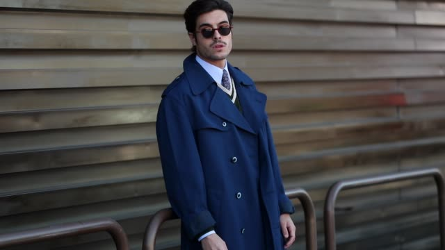 guest is seen wearing blue trench coat, vest, grey pants at fortezza da basso on january 8, 2020 in florence, italy. - トレンチコート点の映像素材/bロール