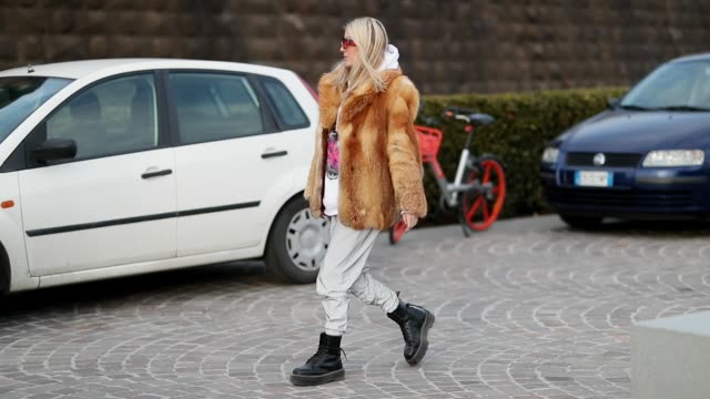 vidéos et rushes de guest is seen wearing boots, fake fur jacket, white pants, sunglasses during the 95th pitti uomo at fortezza da basso on january 9, 2019 in florence,... - bottes