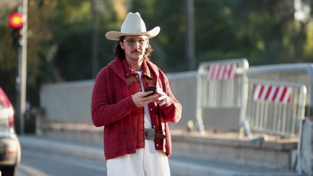 vidéos et rushes de guest is seen wearing cowboy hat red puffer jacket, cardigan, white pants at fortezza da basso on january 9, 2020 in florence, italy. - cardigan