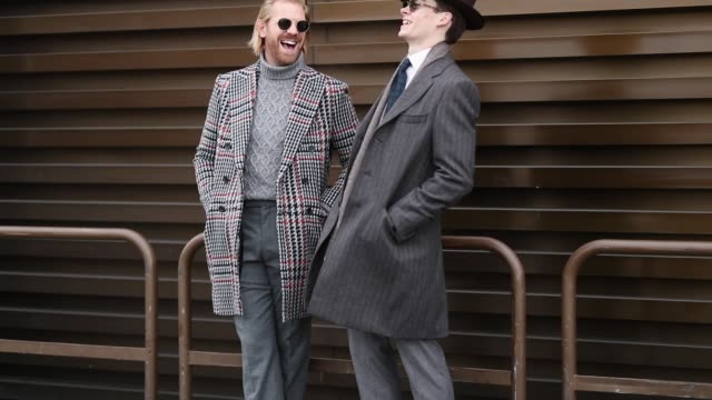 stockvideo's en b-roll-footage met guest is seen wearing grey suit, leather shoes, grey wool coat, hat and a guest wearing grey turtleneck, plaid coat, grey pants during the 95th pitti... - herenkleding