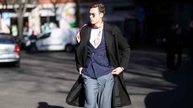 A guest is seen wearing navy blazer black wool coat grey pants sunglasses during Milan Menswear Fashion Week Autumn/Winter 2019/20 on January 14 2019...