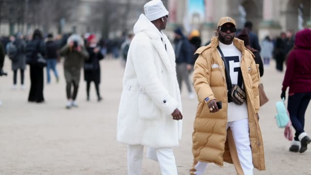 stockvideo's en b-roll-footage met guest is seen wearing white coat, bucket hat, cycle sunglasses and johnson gold is seen wearing beige puma down feather puffer coat outside kenzo... - herenkleding