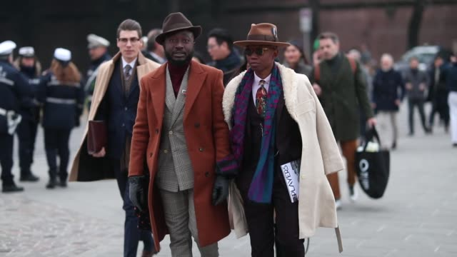 A guest is seen wearing wool coat hat grey suit and a guest wearing tie hat suit creme white wool coat during the 95th Pitti Uomo at Fortezza Da...