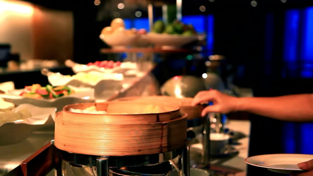 guest picking dimsum from buffet line in hotel restaurant - buffet stock videos & royalty-free footage
