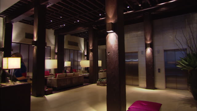 a guest walks away from the front desk in the lobby of a hotel. - 高級ホテル点の映像素材/bロール