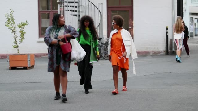 A guest wearing a blazer and a red bag second guest wearing green top and third guest wearing orange dress during Oslo Runway SS19 on August 14 2018...