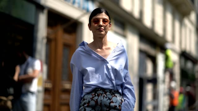 A guest wearing a blue button shirt with wide sleeves wide leg pants with floral print during Paris Fashion Week Menswear Spring/Summer 2018 on June...