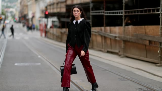 A guest wearing a bordeaux red cropped pants and black knit is seen during Oslo Runway SS19 on August 15 2018 in Oslo Norway