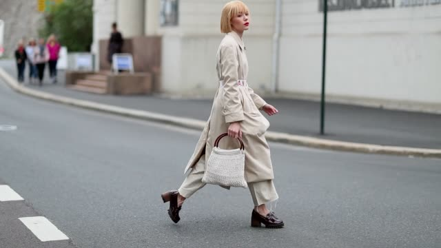 A guest wearing a creme white bag pants and trench coat is seen during Oslo Runway SS19 on August 15 2018 in Oslo Norway