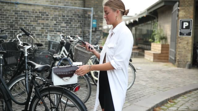 vídeos y material grabado en eventos de stock de a guest wearing a cycle pants white long button shirt bag sneakers seen during the copenhagen fashion week spring/summer 2019 on august 7 2018 in... - camisa