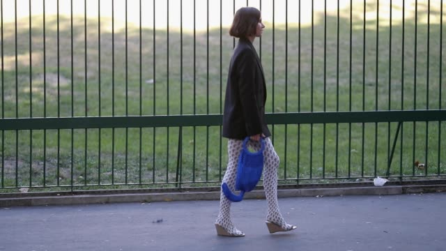 A guest wearing blazer blue net bag tights with print seen outside Koche during Paris Fashion Week Womenswear Spring/Summer 2019 on September 25 2018...