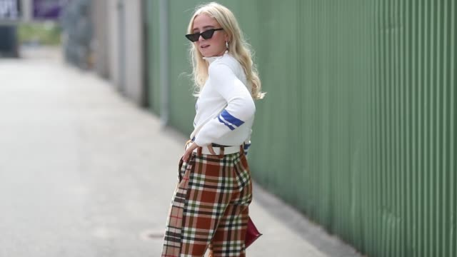 vídeos de stock e filmes b-roll de a guest wearing checked flared pants with slit and long shirt with no apres ski print is seen outside jlindeberg during the copenhagen fashion week... - copenhaga