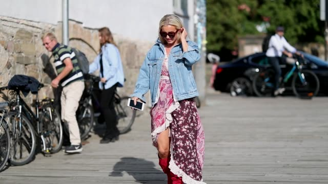 A guest wearing dress with slit denim jacket during Oslo Runway SS19 on August 14 2018 in Oslo Norway