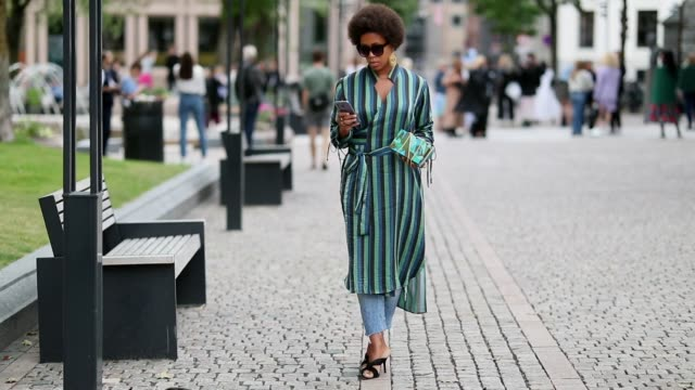 A guest wearing green striped dress and denim jeans during Oslo Runway SS19 on August 14 2018 in Oslo Norway