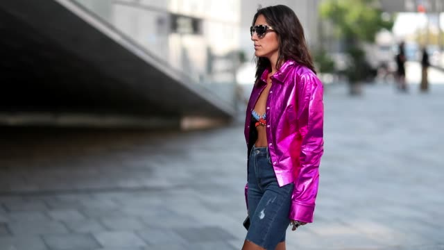 A guest wearing pink jacket cropped denim jeans ankle boots with snake print glitter bag outside Designers Rmx during the Copenhagen Fashion Week...