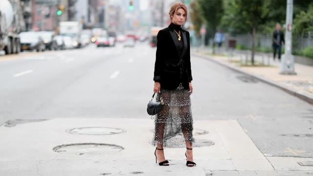 vidéos et rushes de a guest wearing sheer dress blazer jacket dior saddle bag heels seen outside oscar de la renta during new york fashion week spring/summer 2019 on... - robe