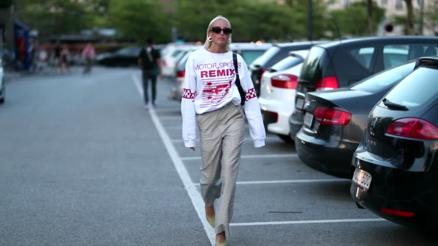 vídeos de stock e filmes b-roll de a guest wearing white cropped long shirt with red name print high waisted checked pants is seen outside saks potts during the copenhagen fashion week... - copenhaga