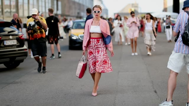 A guest wearing white cropped top red midi skirt pink blazer is seen outside Ganni during the Copenhagen Fashion Week Spring/Summer 2019 on August 9...