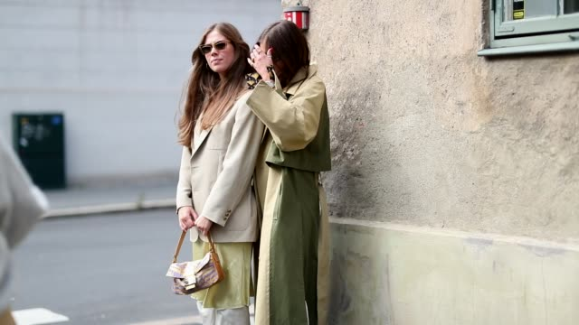 A guest wearing white pants mustard dress beige brown blazer and Darja Barannik wearing beige trench coat with slits creme white rolled pants ankle...