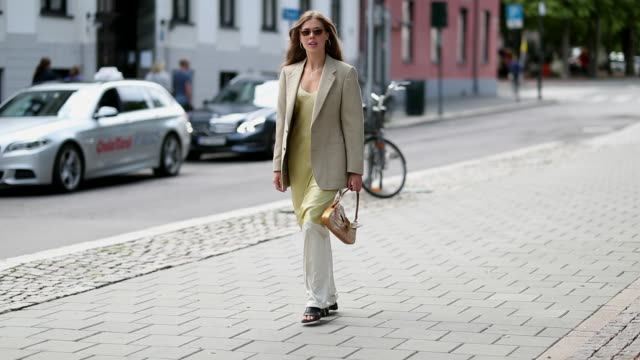 A guest wearing white pants mustard dress beige brown blazer during Oslo Runway SS19 on August 14 2018 in Oslo Norway