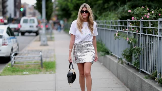 a guest wearing white tshirt and glitter mini skir during new york fashion week spring summer 2019 on september 07 2018 in new york city - maglietta video stock e b–roll