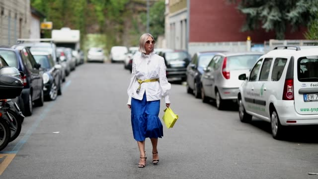 A guest wearing yellow bag blue skirt and white jacket on September 19 2018 in Milan Italy