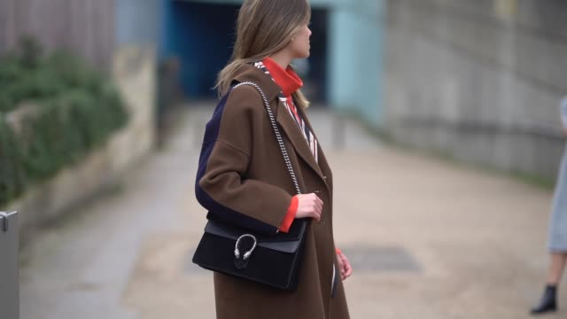 stockvideo's en b-roll-footage met a guest wears a a gucci bag a brown coat an orange turtleneck checked pants during london fashion week february 2018 on february 18 2018 in london... - coltrui