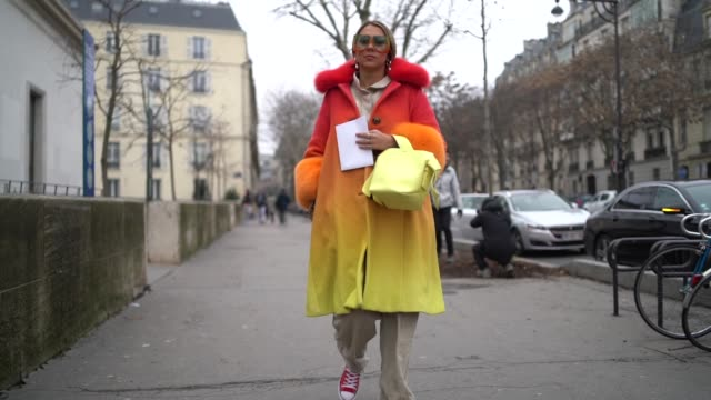 A guest wears a a red orange and yellow fluffy coat a yellow bag oversize flare pants red sneakers sunglasses earrings during Paris Fashion Week...