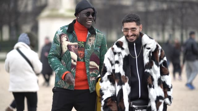 vidéos et rushes de a guest wears a beanie hat a green jacket with floral and animal print a red wool turtleneck a guest wears sunglasses a beard a white brown and black... - chapeau