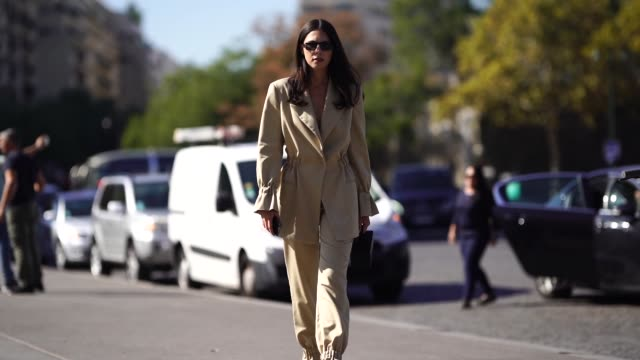 A guest wears a beige blazer jacket flare pants outside Ann Demeulemeester during Paris Fashion Week Womenswear Spring/Summer 2019 on September 27...