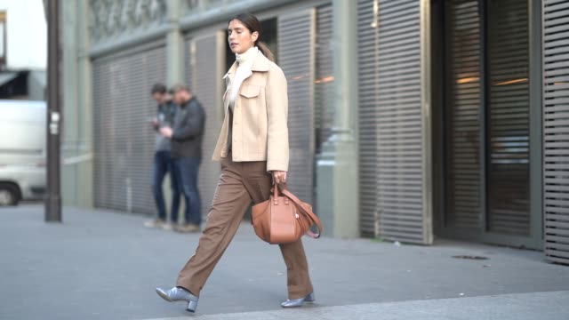 A guest wears a beige jacket a white turtleneck brown flare pants blue shoes a leather bag outside Ralph Russo during Paris Fashion Week Haute...