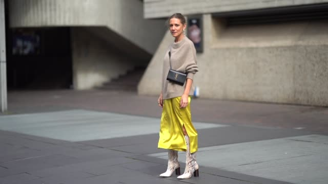 guest wears a beige wool pullover, a black ysl saint laurent bag, a yellow silk skirt, snake print boots, earrings, during london fashion week... - street style stock videos & royalty-free footage