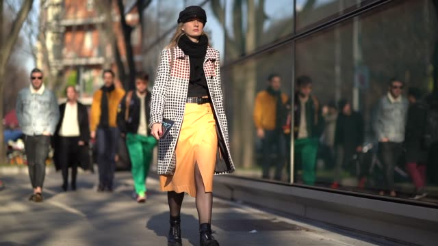 A guest wears a beret hat a skirt and a coat with polka dots during Milan Menswear Fashion week Fall/Winter 2018/19 on January 13 2018 in Milan Italy