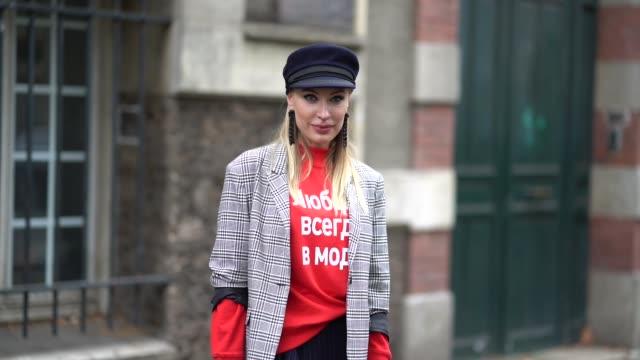 a guest wears a beret hat a tartan blazer jacket a red pull over a skirt black boots a red bag outside valentino during paris fashion week womenswear... - tartan video stock e b–roll