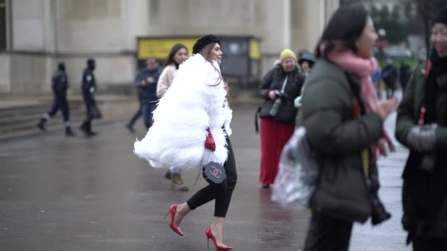 A guest wears a beret hat a white faux fur fluffy coat a bag in the shape of a rose a bow tie a white top with buttons black pants red shoes during...