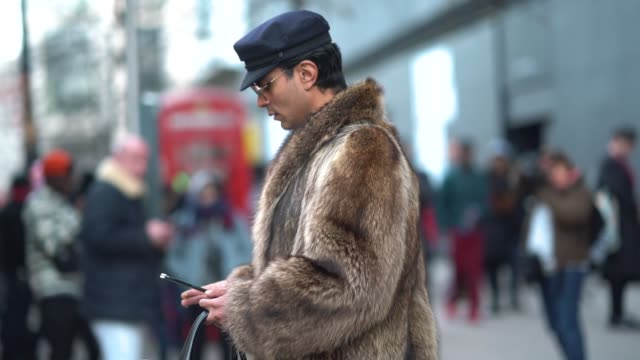 A guest wears a beret hat and a fur coat during London Fashion Week Men's January 2018 at on January 06 2018 in London England