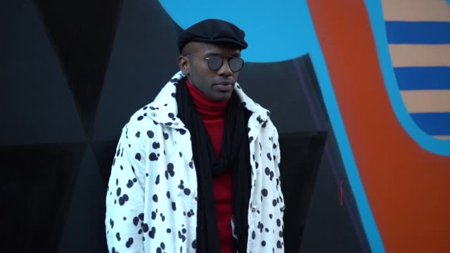 A guest wears a beret hat sunglasses a white coat with black dots a red turtleneck a clutch black shoes during London Fashion Week Men's January 2018...