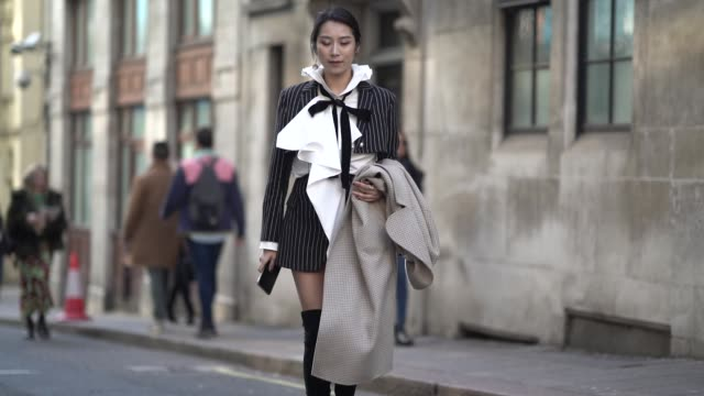 guest wears a black and white striped blazer jacket, a white oversized shirt, a black tie, high boots, during london fashion week february 2019 on... - shirt and tie bildbanksvideor och videomaterial från bakom kulisserna