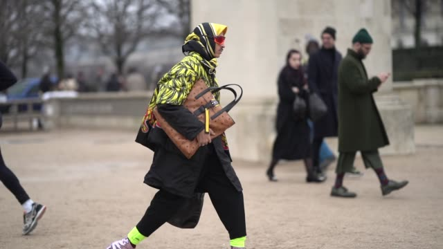 A guest wears a black and yellow scarf a black yellow and red padded jacket black pants with yellow hem shiny metallic pale pink boots with separated...