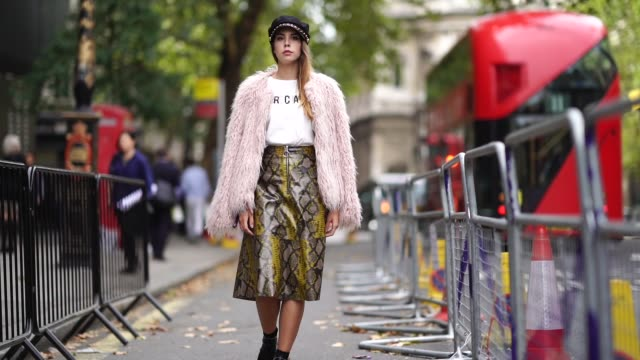 A guest wears a black beret a pink faux fur coat a white tshirt a snake print leather skirt black leather shoes during London Fashion Week September...
